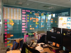 glass wall with grid of stick notes and large 2015 year planner in top-right corner