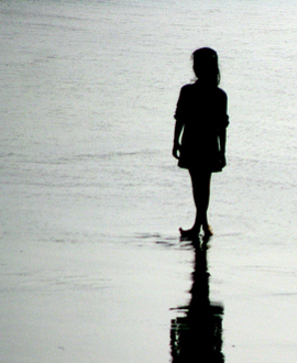 silhouette of a girl on a beach with shadow reflection in the wet sand