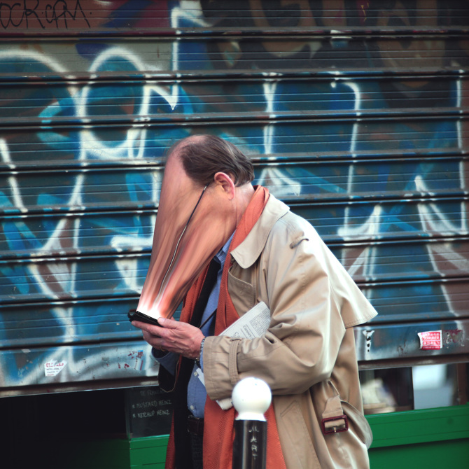 man looking into cell phone with face stretched appearing to be sucked into or glued onto the screen